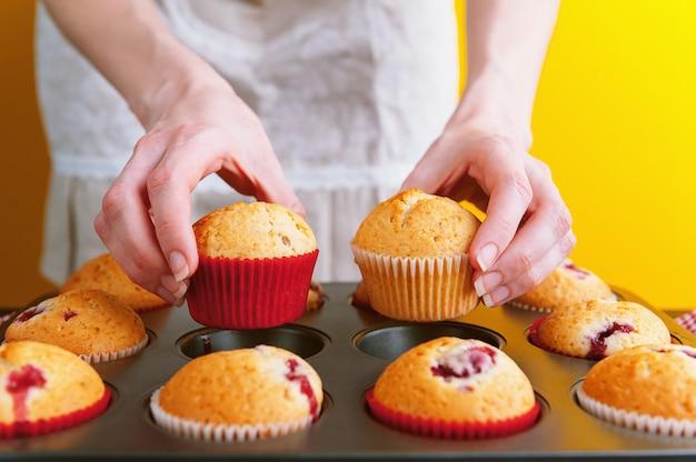 Chef com muffins em uma superfície amarela brilhante
