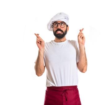 Chef com os dedos cruzados sobre fundo branco