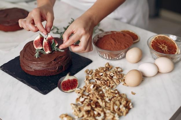 Chef com roupas brancas prepara um bolo de chocolate. lady está preparando a sobremesa. mulher faz um bolo.