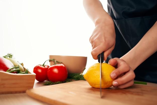 Chef com uma faca nas mãos corta legumes e limão cozinhando em casa