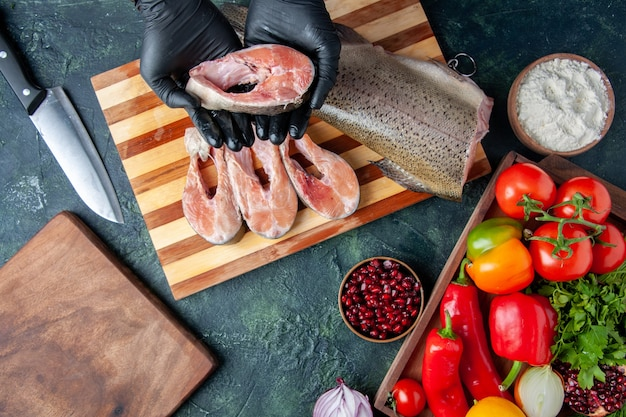 Chef com vista de cima segurando vegetais crus em fatias de peixe na tábua de servir de madeira na mesa da cozinha