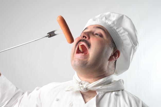 Chef comendo uma salsicha