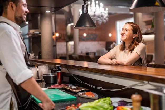 Chef confiante em pé no balcão da cozinha aberta e conversando com o hóspede do restaurante