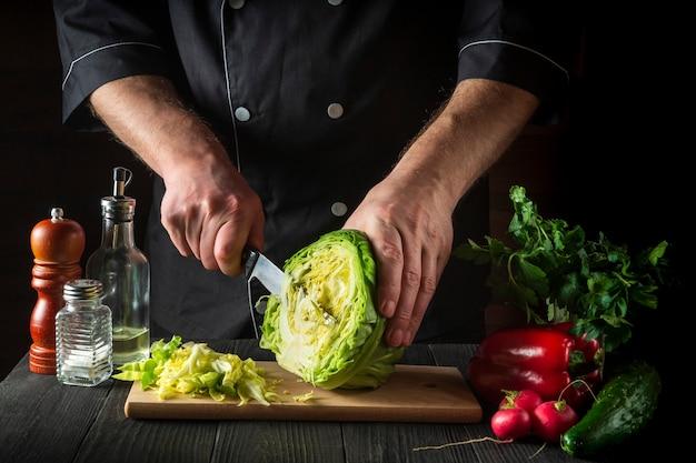 Chef corta repolho fresco com uma faca para salada em uma mesa de cozinha vintage com legumes frescos