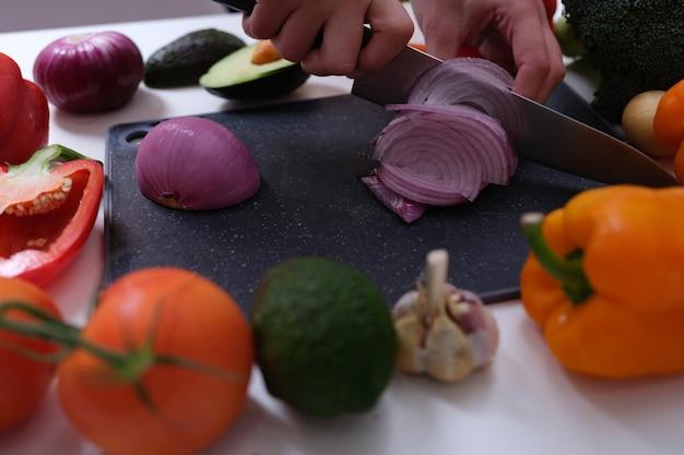 Chef cortando cebola roxa a bordo entre vegetais closeup