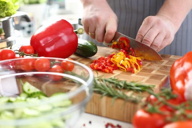 Chef cortando ingredientes de salada de vegetais orgânicos
