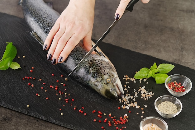 Chef cortando salmão fresco na cozinha. chef mulher corta salmão em pedaços