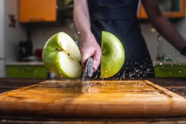 Chef cortando uma maçã verde ao meio com uma grande faca em movimento