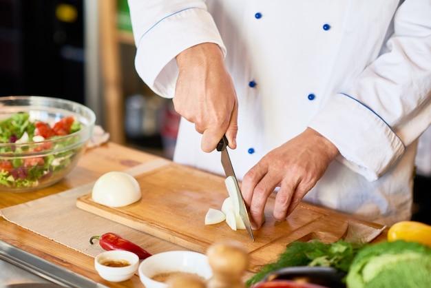 Chef cortar cebolas para salada