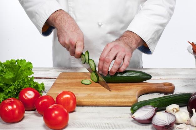 Chef, corte um pepino verde em sua cozinha