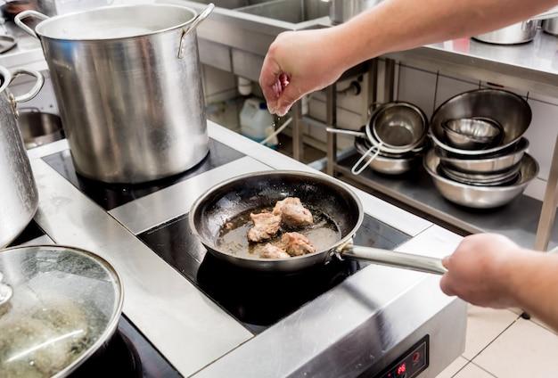 Chef cozinha batatas fritas com pedaços de carne em uma cozinha de restaurante