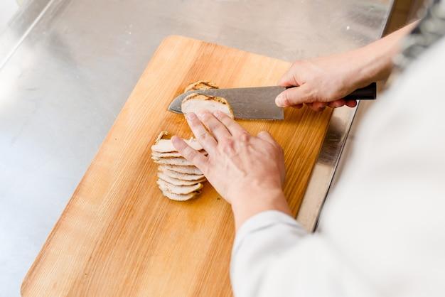 Chef cozinha carne com faca em restaurante