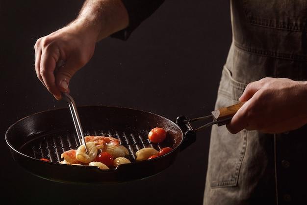 Chef cozinha frutos do mar, camarão em uma panela com legumes