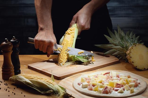 Chef cozinhando pizza havaiana, cortando milho fresco