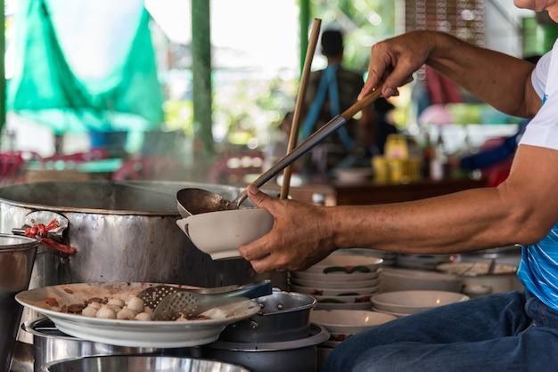 Chef cozinhando uma sopa de macarrão no mercado de comida de rua