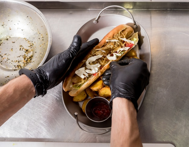 Chef cozinhar cachorro-quente em uma grade. restaurante.