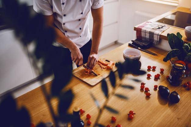Chef criativo caucasiano em pé na cozinha e cortar salmão no almoço.