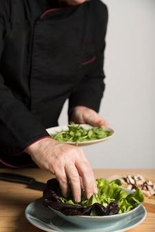 Chef de alto ângulo, cozinhar salada