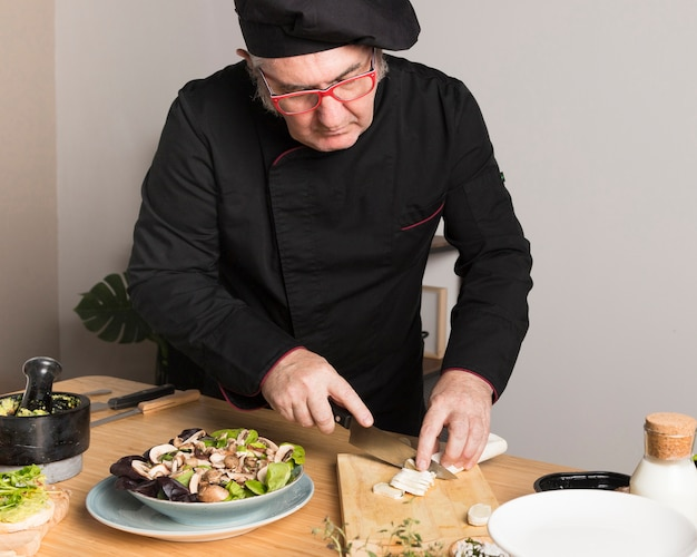 Chef de alto ângulo fatiar ingredientes para salada