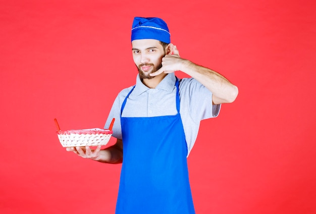 Chef de avental azul segurando uma cesta de pão coberta com uma toalha vermelha e pedindo uma ligação.