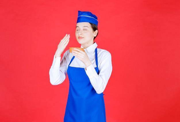 Chef de avental azul segurando uma tigela de cerâmica e cheirando o sabor.