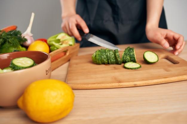 Chef de avental preto cortando vegetais, trabalho doméstico, cozinhar