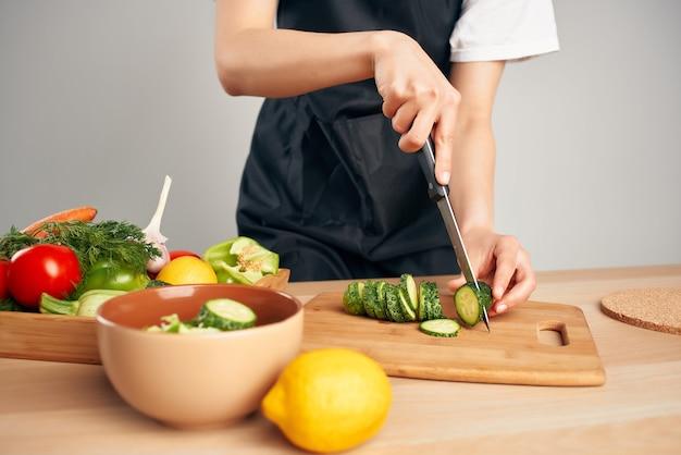 Chef de avental preto, corte de legumes, trabalho doméstico, cozinhar. foto de alta qualidade
