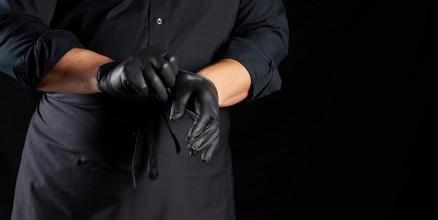 Chef de camisa preta e avental coloca luvas de látex pretas nas mãos antes de preparar a comida, preta