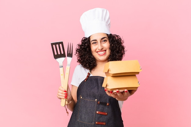 Chef de churrasco árabe bonito com hambúrgueres take away