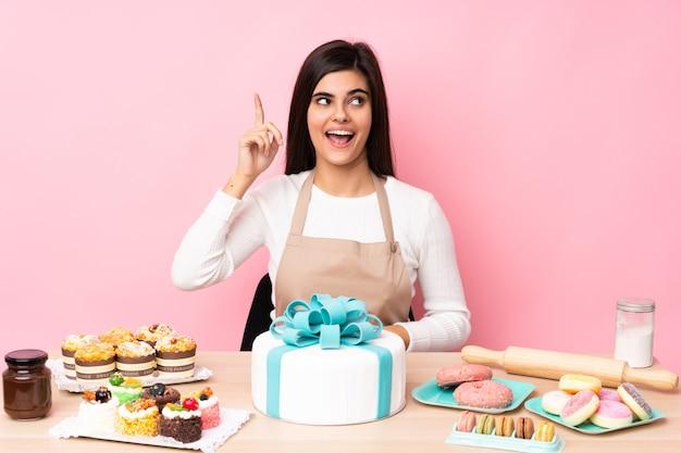 Chef de confeitaria com um grande bolo em uma mesa sobre uma parede rosa isolada com a intenção de realizar a solução enquanto levanta um dedo