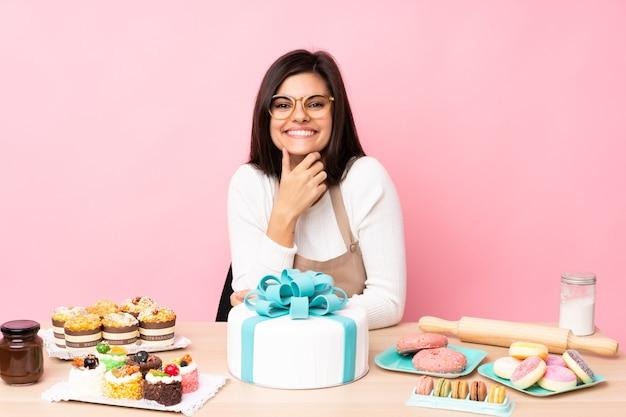 Chef de confeitaria com um grande bolo em uma mesa sobre uma parede rosa isolada com óculos e sorrindo