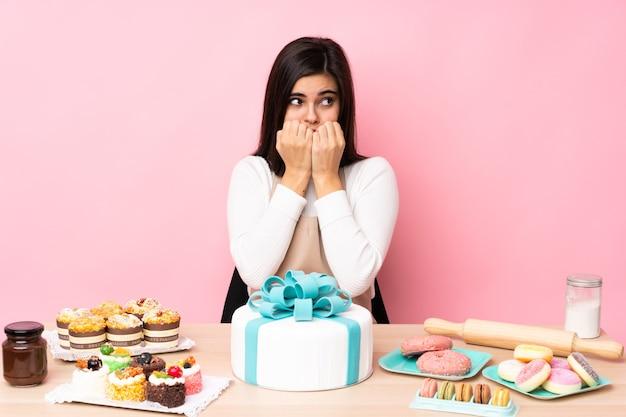 Chef de confeitaria com um grande bolo em uma mesa sobre uma parede rosa isolada nervoso e com medo de colocar as mãos na boca