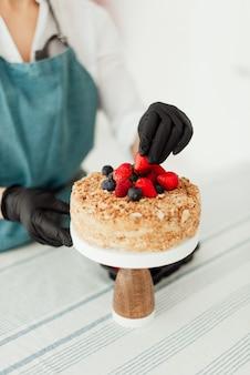 Chef de confeitaria preparando bolo de mel decorado com frutas doces em close-up