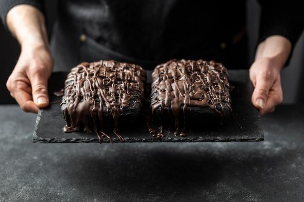 Chef de confeitaria segurando dois bolos de chocolate