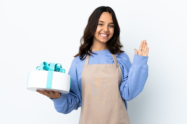 Chef de confeitaria segurando um grande bolo isolado saudando com a mão com expressão feliz