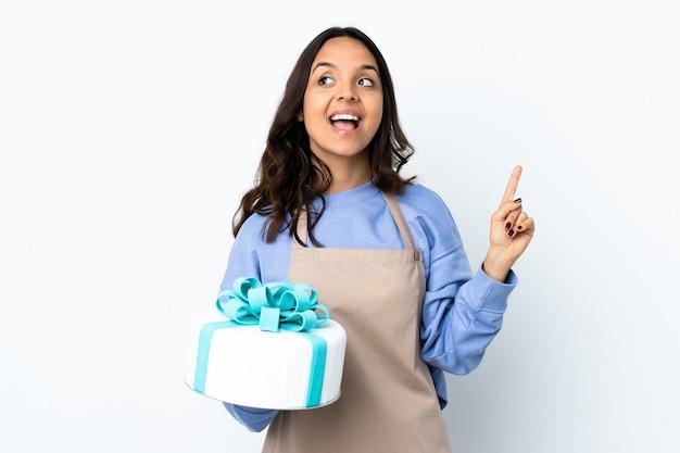 Chef de confeitaria segurando um grande bolo sobre uma parede branca isolada com a intenção de descobrir a solução enquanto levanta um dedo