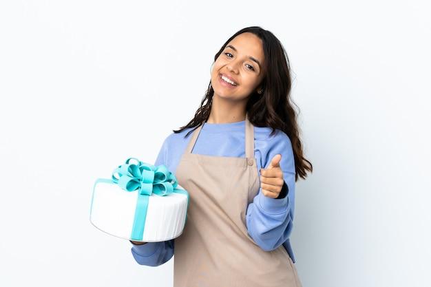 Chef de confeitaria segurando um grande bolo sobre uma parede branca isolada com o polegar para cima porque algo bom aconteceu