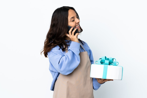 Chef de confeitaria segurando um grande bolo sobre uma parede branca isolada, conversando com alguém ao telefone celular