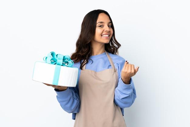 Chef de confeitaria segurando um grande bolo sobre uma parede branca isolada, convidando a vir com a mão. feliz que você veio