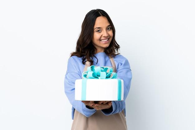 Chef de confeitaria segurando um grande bolo sobre uma parede branca isolada segurando copyspace imaginário na palma para inserir um anúncio