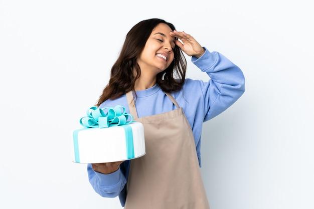 Chef de confeitaria segurando um grande bolo sobre uma parede branca isolada sorrindo muito