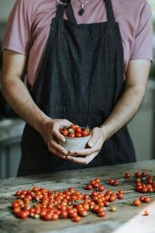 Chef de cozinha com tomates-cereja vermelhos