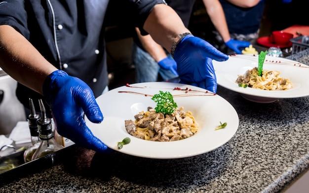 Chef de cozinha macarrão com carne na panela. cozinha de estilo italiano. restaurante.