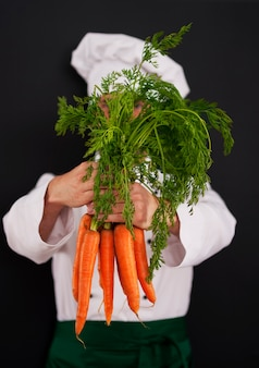 Chef de cozinha segurando um monte de cenouras frescas