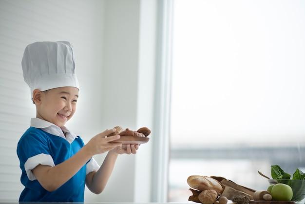 Chef de criança oferecendo café da manhã, pão e frutas