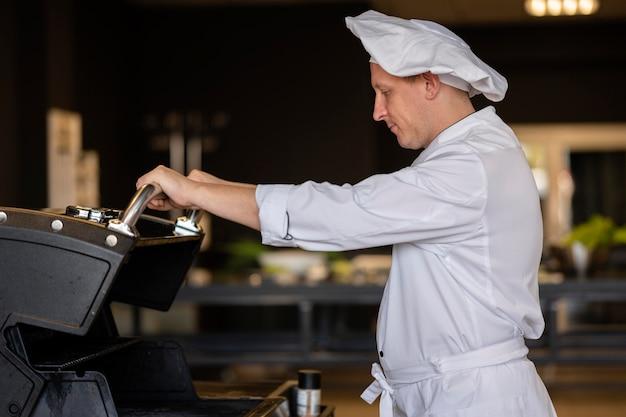 Chef de dose média fazendo churrasco