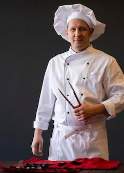 Chef de dose média segurando uma ferramenta de churrasco