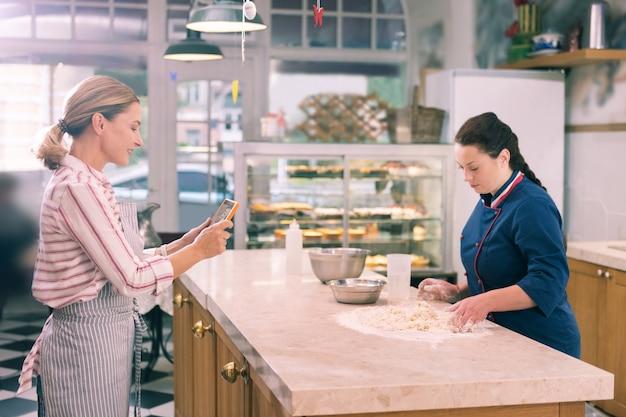 Chef de filmagem. dona de uma padaria loira filmando seu chef cozinhando croissants para curso on-line