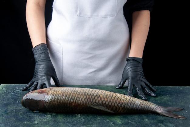 Chef de frente para o avental em pé atrás da mesa com peixe cru