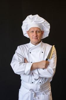 Chef de frente segurando uma faca